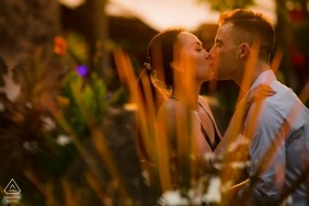 A couple in Saigon kisses in a garden at dusk during their pre-wedding photoshoot by a Ho Chi Minh, Vietnam photographer.