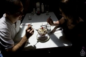 Engaged couple sharing an ice cream sundae at the Peninsula Creamery in Palo Alto, CA