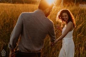 Um casal tem as mãos e anda através de um campo ensolarado de grama alta em Dois Irmaos nesta foto de noivado por um fotógrafo do Rio Grande do Sul, Brasil.