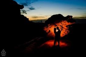 Un couple à Lavras Novas est silhouette alors qu'ils se tiennent devant une grande formation rocheuse au crépuscule lors de cette séance photo précédant le mariage par un photographe de Minas Gerais, au Brésil.