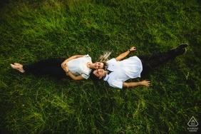 Para leży razem na trawie w Ouro Preto podczas sesji zaręczynowej wykonanej przez brazylijskiego fotografa Minas Gerais.