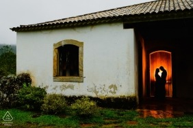 A couple in Ouro Preto can be seen standing together inside a house in this engagement photo by a Minas Gerais, Brazil photographer.