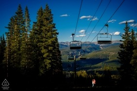 A couple stands beneath a ski lift in spring in Breckenridge as the sun and trees cast pockets of light in this engagement photoshoot by a Colorado photographer.