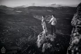 Una pareja se toma de la mano mientras se paran en una roca en Rocca Calascio con vistas a las llanuras en esta sesión de compromiso de un fotógrafo de Lazio, Italia.
