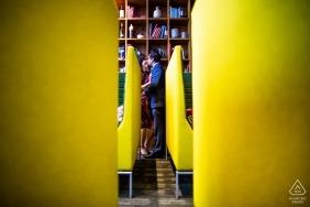 In diesem Verlobungsporträt eines Fotografen aus San Francisco, CA, ist ein Paar zu sehen, das sich durch eine Reihe gelber Bänke küsst.