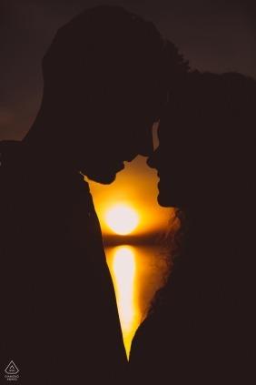 Silhoutted-paar delen een moment tijdens hun pre-huwelijkssessie in Bolsena, Italië