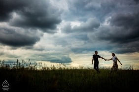A couple walks together in Brno beneath a dramatic and dark sky in this engagement session by a Prague photographer