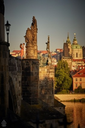 Engaged couple stand atop the Charles Bridge during their sunrise portrait sessio
