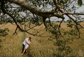 This Engaged couple kiss in a field during their Pre-wedding shoot in Hoi An Vietnam