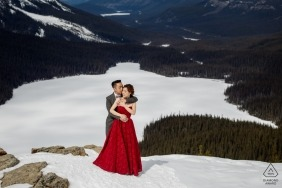 Banff National Park, AB, Canada engagement photographer captured this photo of a couple embracing on top of a snow covered mountain