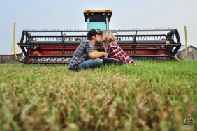 A couple sits in the grass and kisses in front of a tractor in this pre-wedding photo by an Alberta, Canada photographer.