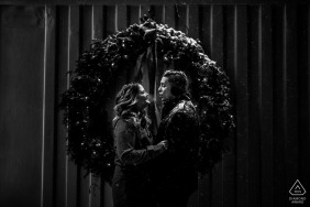 The engaged couple breaths are visible on a cold winter night engagement session at Bentleyville, USA