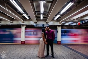 A subway train passes by as the engaged couple kiss during their engagement shoot at the Grand Central Station