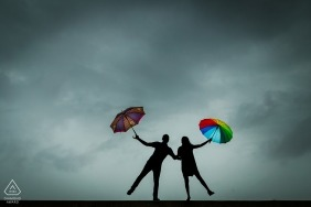 Les silhouettes du couple tenant des parapluies lumineux sur un ciel gris ont été capturées par un photographe de fiançailles à Mumbai