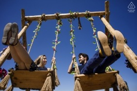 Enagaged couple portrait on swings in cappadocia, turkey for their engagement photo session