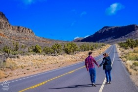 California road portrait of an engaged couple walk at the road