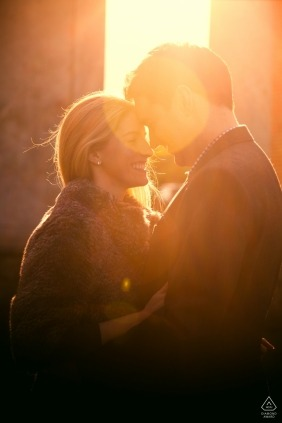 Hertfordshire wedding photographer caught this image of a couple kissing while the sun shines behind them in this engagement photo taken near St. Pauls Walden Bury