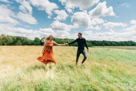 Un couple tient les mains sous un ciel bleu dans ce portrait de prélavage pris par un photographe de fiançailles Overjissel