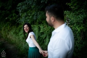 The soon to be bride smiles back at the groom as they walk hand in hand down a path near Rovaglio-Palmi in this photo shot by a Calabria engagement photographer