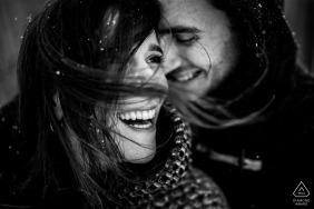A neve cai suavemente ao redor do retrato do casal feliz por um fotógrafo de noivado de Apúlia