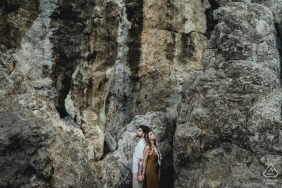 A couple stands back to back in front of a stone cliff in this engagement portrait photographed by a Naples photographer near Positano