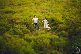 Séance d'engagement dans les prairies avec un couple sautant dans des champs verdoyants