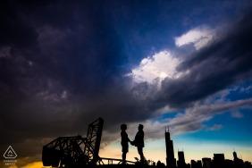 Sessão de casal de Chicago com o horizonte da cidade por trás deles ao pôr do sol