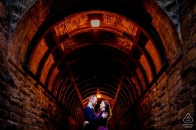 Wilkes Tunnel, Old Town Alexandria VA Engagement Shoot - A couple embraces at the entrance of the tunnel