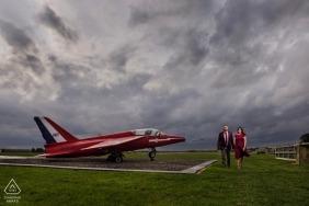 Paar-Verpflichtungs-Porträt mit rotem Kleid und rotem Flugzeug am Cotswald-Flughafen, Großbritannien