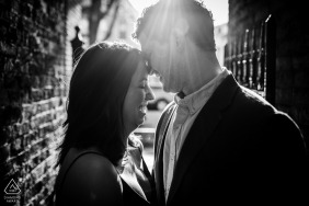 Couple laughs together in a ray of sunlight during an engagement session in Roscoe Village in Chicago.
