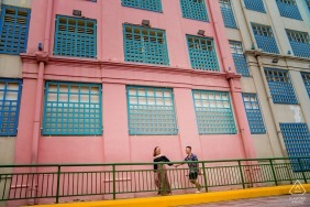 Singapore Industrial Engagement photoshoot with a coule walking hand in hand by pink painted building.