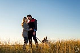 Para i ich szczenię przyjmują ostatnie światło dnia podczas jesiennej sesji zaręczynowej w wysokiej trawie na Plum Island w stanie Massachusetts