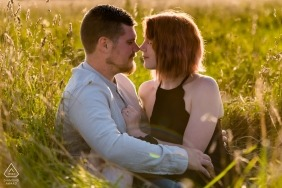 Great Addington, Northamptonshire engagement portrait of couple sitting among the tall grasses in a field.