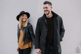 Foto de noivado Gloucestershire de um casal de mãos dadas diante de paredes brancas.