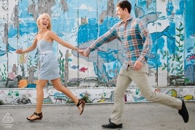 San Diego, California Pre Wedding Photography | Portrait of a Couple holding hands and running on the street next to painted sign
