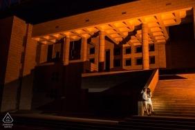 O casal de noivos está de pé na frente de um anfiteatro realçado com cor laranja no campus principal da Universidade de Bilkent, Ancara