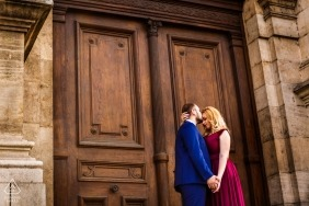 Engaged couple kisses in front of the main entrance of the Appeal Court historical building during pre wedding photo shoot.