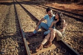 Sessão de retratos pré-casamento no Brasil com casal sentado em trilhos de trem.