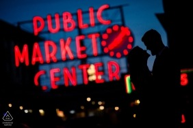 Seattle, WA Public Market Center Engagement photos at the busy Pike Market creates an opportunity for a silhouette portrait.