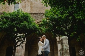 Engagement Photographer for Barcelona - Image contains: couple, trees, arch, building, kiss