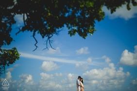 訂婚照片-巴厘島夫婦在日落時與雲彩,藍天和樹木。