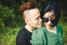 Engagement Photos from YUN NAN - Image contains: hair, wind, green, posing, grass, natural light, couple, sunglasses