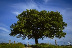 Engagement Portrait from Aachen, Germany - Image contains: couple, tree, fence, grass, blue, sky