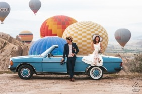 Engagement Photographer for Cappadocia, Turkey - Image contains: couple, blue, car, colorful, hot air balloons