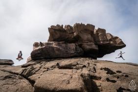 Photographe de fiançailles pour Tregastel, France - Portrait de pré-mariage avec couple sautant dans les rochers