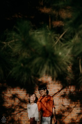 Engagement Photographer for Dalat, Vietnam - Image contains: couple, shadows, trees, pine, wood