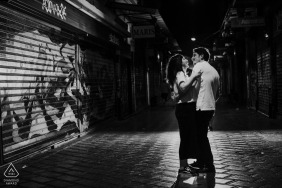 Engagement Photos from Athens, Greece - ICouple standing on narrow street full of graffitis is hugging and laughing