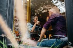 Un couple boit du café ensemble à Cherry Street à Philadelphie pendant leur séance de portrait de fiançailles