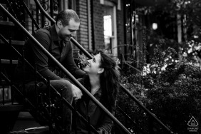 Villeray, Montreal, Canada — Black and white engagement photo of couple sitting on stairs in front of their Montreal apartment