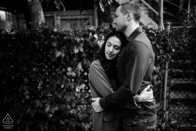 Montreal, Quebec engagement portrait photographer | Black and white photo of couple hugging in Montreal alleyway, with backyard vines behind them